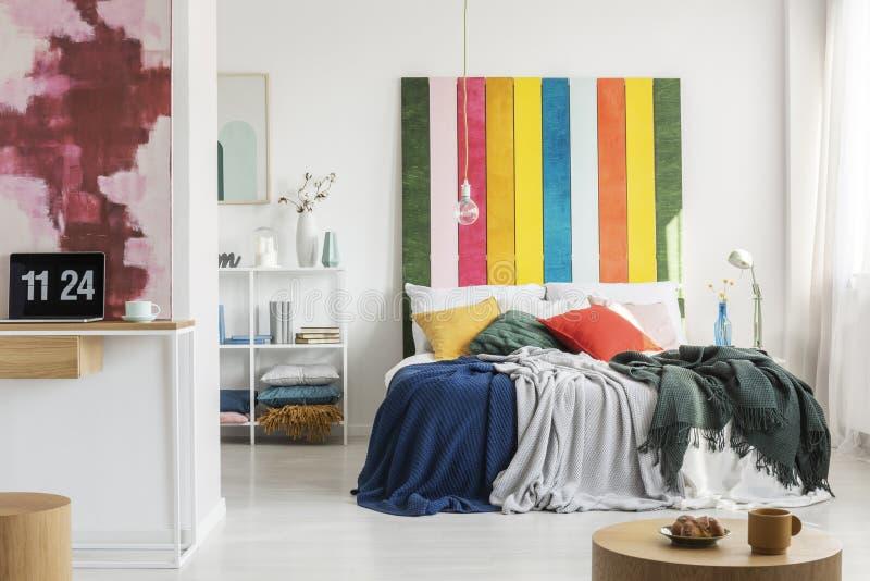 Het binnenland van de moderne, open plekflat met een huisbureau in de voorgrond en een slaapkamer met een kleurrijke bedhead op d royalty-vrije stock fotografie