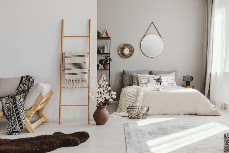 het binnenland van de open plekslaapkamer met venster met gordijnen, spiegel en klok op de muur, ladder met deken, stock fotografie