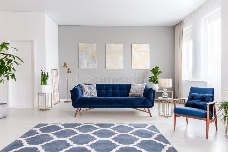 Het binnenland van de open plekwoonkamer met een marineblauwe bank en een leunstoel Deken op de vloer en grafische decoratie op d stock foto's