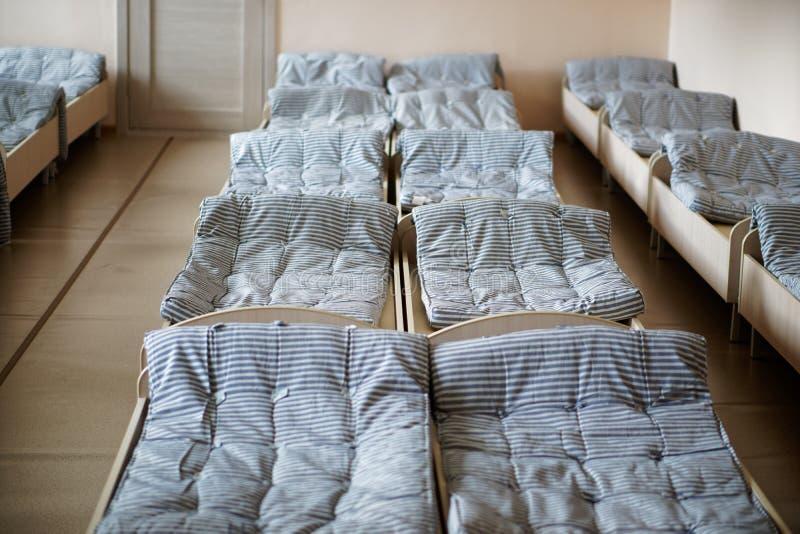 Het binnenland van de slaapkamer van verkenner bereidt in het kamp van de de zomerkinderen de weg Heel wat bedden en ascetische a royalty-vrije stock foto