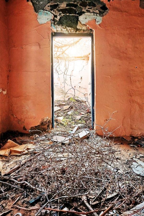 Het binnenland van a desolated oud landelijk huis met lichtrose gebarsten muren, losgemaakte die deur en een vloer met modder wor royalty-vrije stock foto