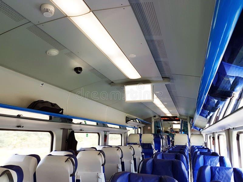 Het binnenland van een moderne personenauto van de daghoge snelheid in blauwe en witte kleuren Zachte zetels voor mensen in openb stock foto