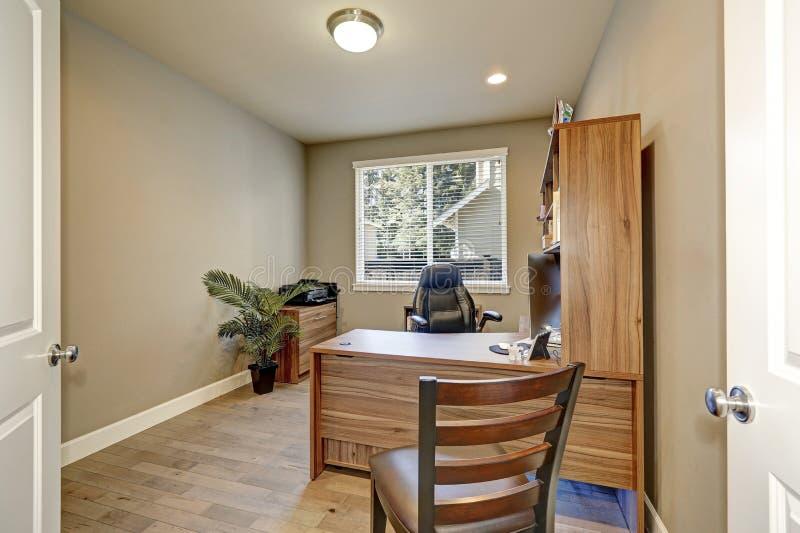Het binnenland van het huisbureau met houten meubilair en leerleunstoel stock foto's