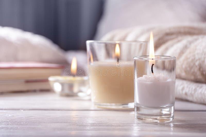 Het binnenland van het huis Stilleven met detailes Verscheidene kaarsen op witte houten lijst voor bed, het concept cosiness stock foto