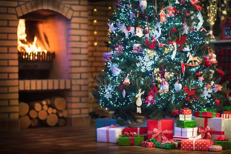 Het binnenland van het Kerstmishuis met boom en open haard stock foto