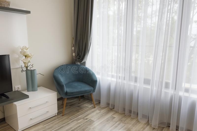 Het binnenland van moderne ruimte met comfortabele leunstoel dichtbij aan groot venster met wijkt en grijze gordijnen af royalty-vrije stock foto