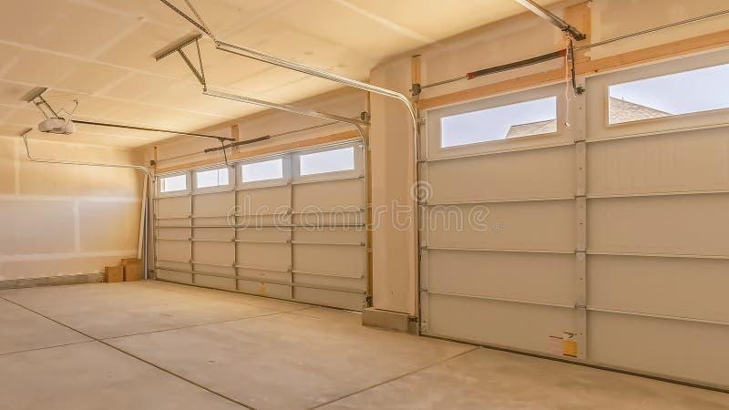 Het Binnenland van het panoramakader van een lege garage met twee grote deuren en kleine rechthoekige vensters stock afbeelding