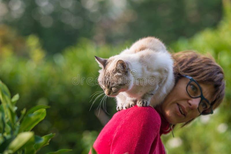 Het binnenlandse kat spelen op de schouder van glimlachende mooie vrouw Het openlucht plaatsen in huistuin royalty-vrije stock afbeeldingen