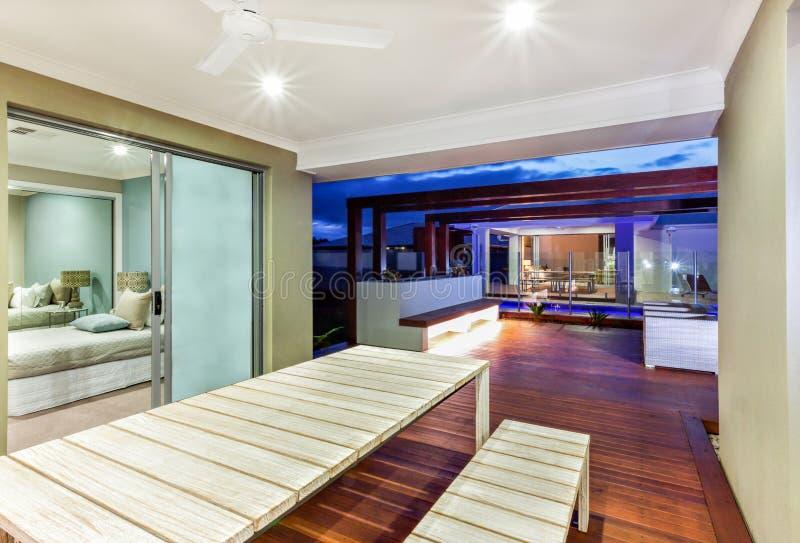 Het binnenlandse ligting van een modern huis met terrasgebied bij nacht stock afbeelding