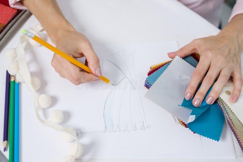 Het binnenlandse ontwerperwijfje trekt bij bureau in bureau met potlood stock afbeeldingen