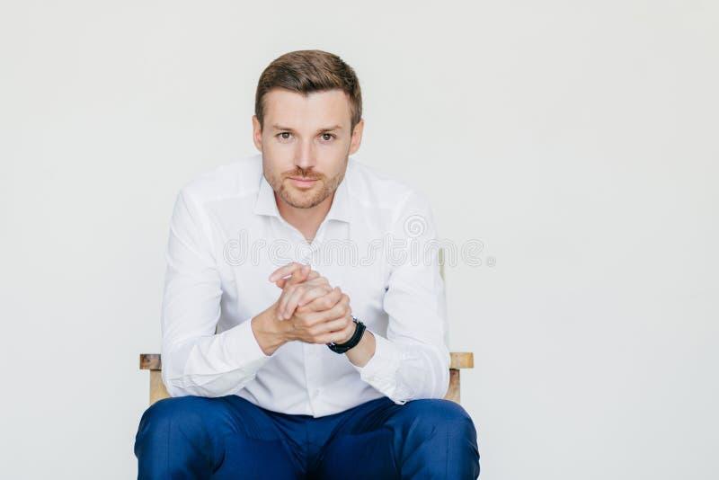 Het binnenportret van knappe zelf zekere zakenman in wit overhemd en zwarte broeken, kijkt met ernstige uitdrukking, klaar aan stock afbeeldingen