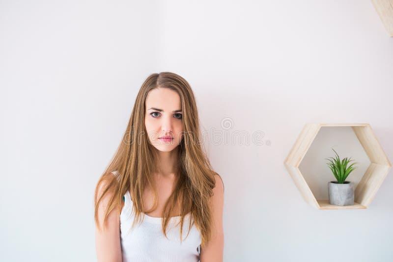 Het binnenportret van mooi vrouwelijk model met gezonde huid en het bruine lange haar die bij camera met ernstige nadenkend stare royalty-vrije stock fotografie