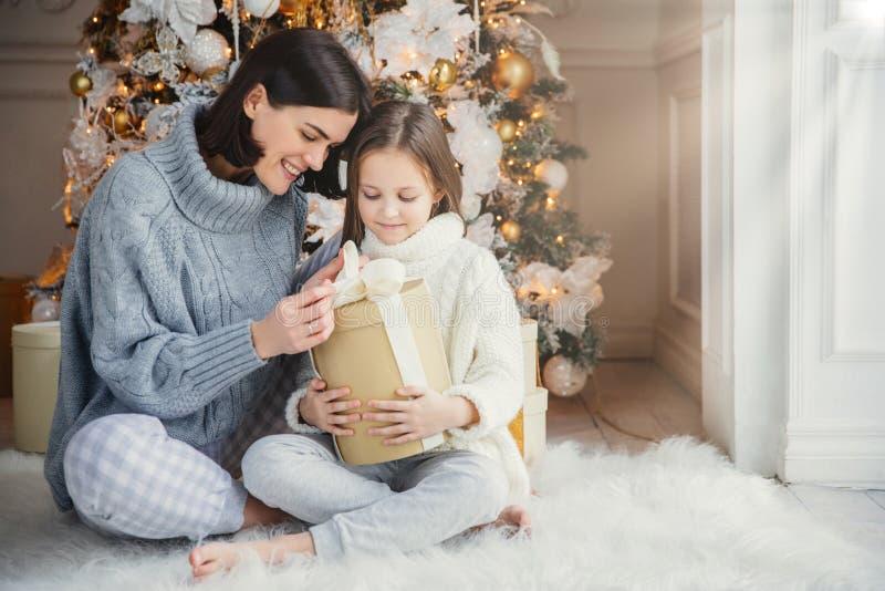Het binnenschot van aanbiddelijk meisje en haar moeder zitten gekruiste benen, open verpakte huidige doos, hebben intrige wat daa stock foto