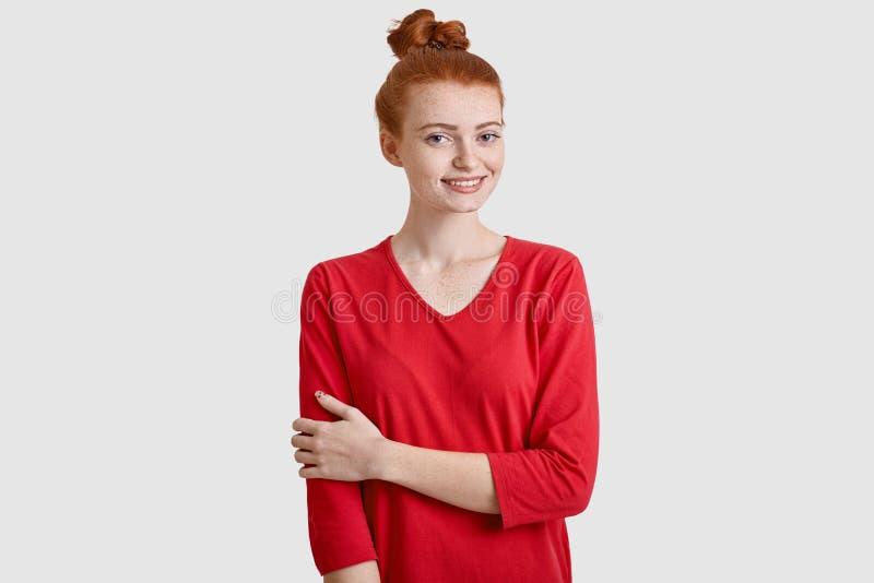 Het binnenschot van blije rode haired vrouw met haarbroodje, houdt handen gekruist gedeeltelijk, draagt rode sweater, heeft freck stock afbeelding