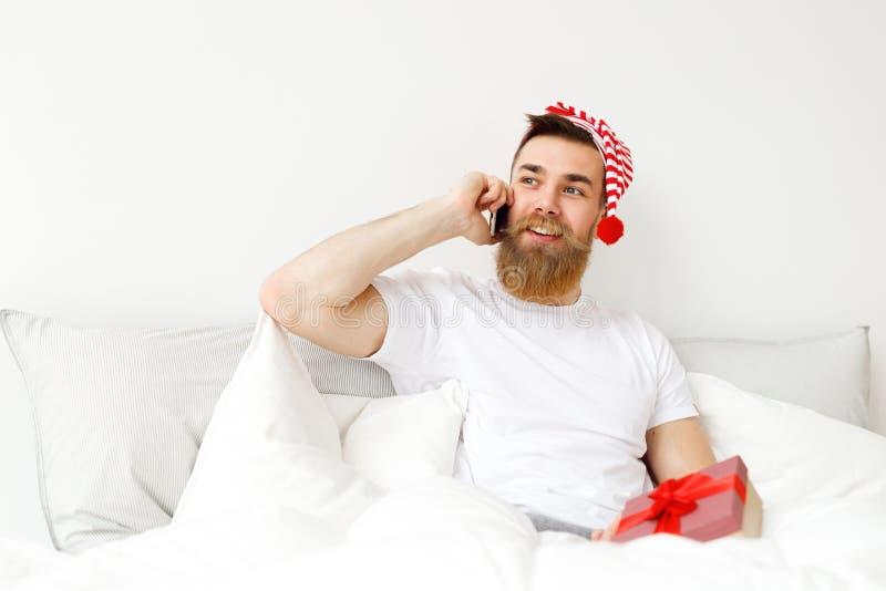 Het binnenschot van de aantrekkelijke mens met dik lange baard en snor spreekt over mobiele telefoon, zit in comfortabel bed royalty-vrije stock afbeelding