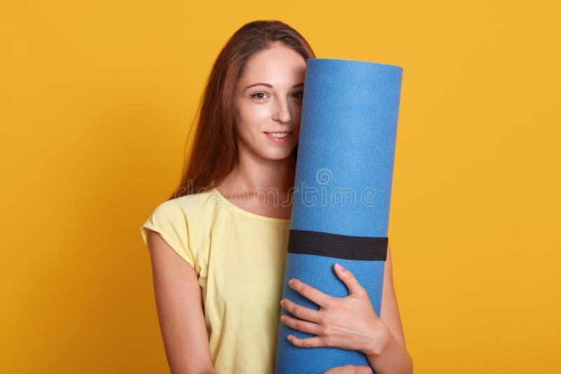 Het binnenschot van jonge mooie vrouwenatleet die t-shirt dragen bevindt zich houdend blauwe geschiktheidsmat en bekijkend camera stock afbeelding