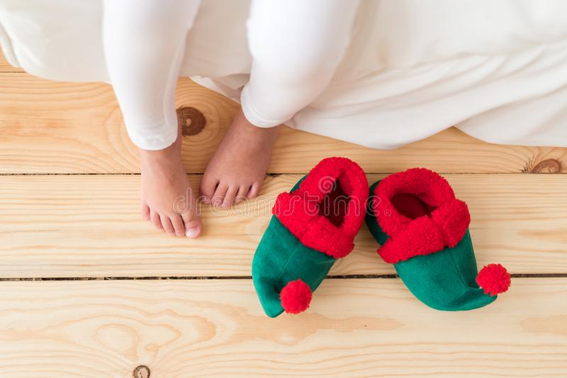 Het binnenschot van kinds naakte voeten bevindt zich op houten vloer, dichtbij elfs schoenen, awakes vroeg in ochtend, die gang g stock afbeelding