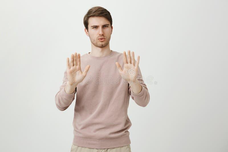 Het binnenschot van knap Europees mannelijk vertrouwen uitdrukken en model die houdt of greep op gebaar terwijl kalm het zijn ton stock foto