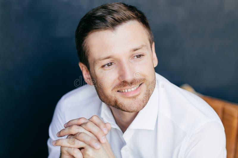 Het binnenschot van knap ongeschoren mannetje met charmante glimlach, draagt elegant wit die overhemd, in afstand wordt geconcent stock afbeelding