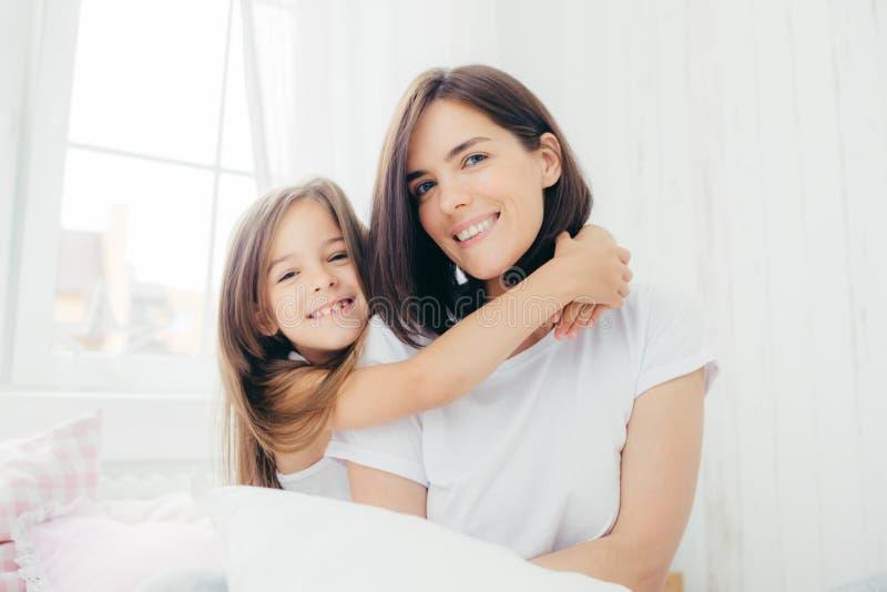 Het binnenschot van knappe donkerbruine moeder met zachte glimlach en haar kleine dochter geeft omhelzing, geniet van binnenlands stock afbeeldingen