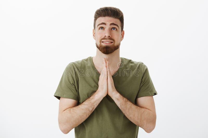 Het binnenschot van leuke vriend biddende god die omhoog als holdingspalmen bidt samen kijken binnen over borst makend wens stock foto's