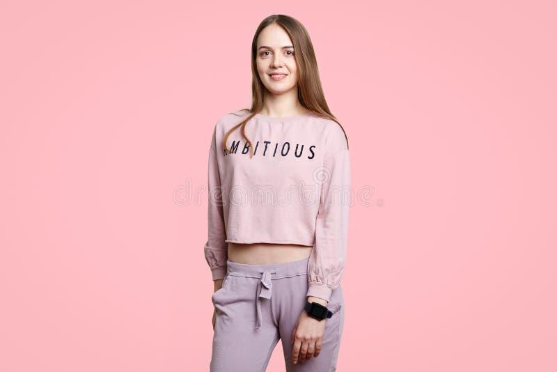 Het binnenschot van mooi wijfje met gezonde huid, draagt toevallige overmaatse sweater en de broeken, geniet van vrije tijd, heef stock foto's