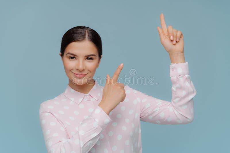 Het binnenschot van mooie donkerbruine damepunten naar omhoog met beide voorvingers, heeft gelukkige uitdrukking, draagt stipblou stock afbeelding