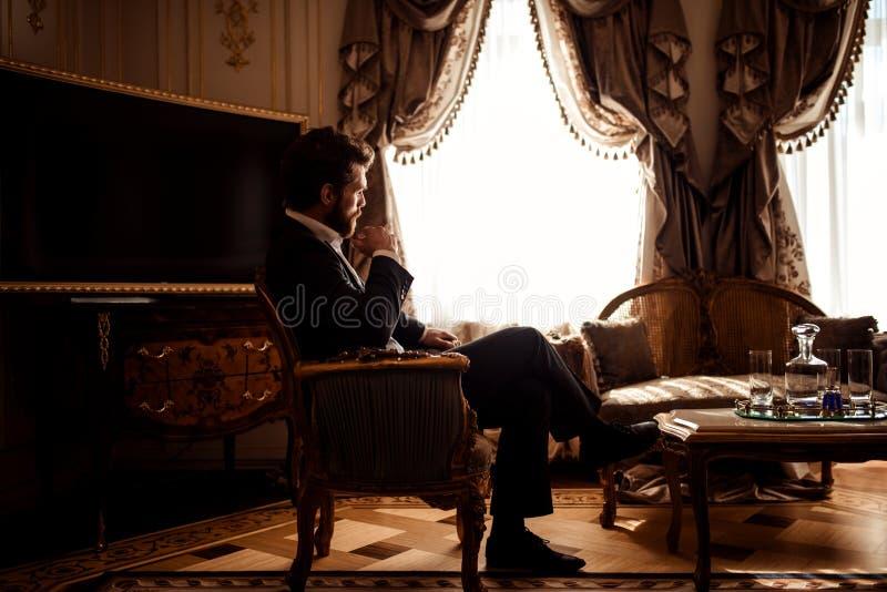 Het binnenschot van nadenkende schitterende zakenman of ondernemer draagt zwart kostuum, zit in comfortabele ruimte met luxueus stock afbeelding