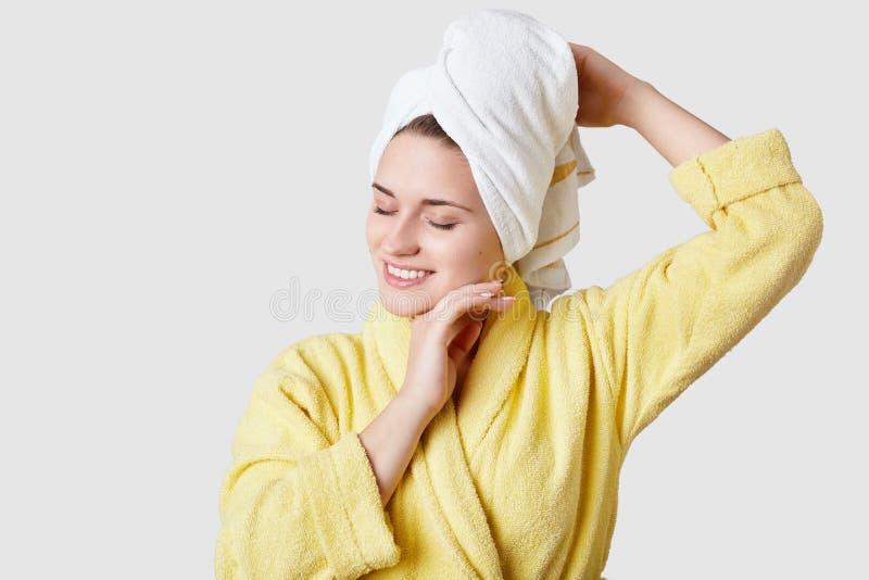 Het binnenschot van ontspannen gelukkige jonge vrouw heeft zachte huid, draagt gele badjas en de handdoek op hoofd, raakt wang, h royalty-vrije stock foto's