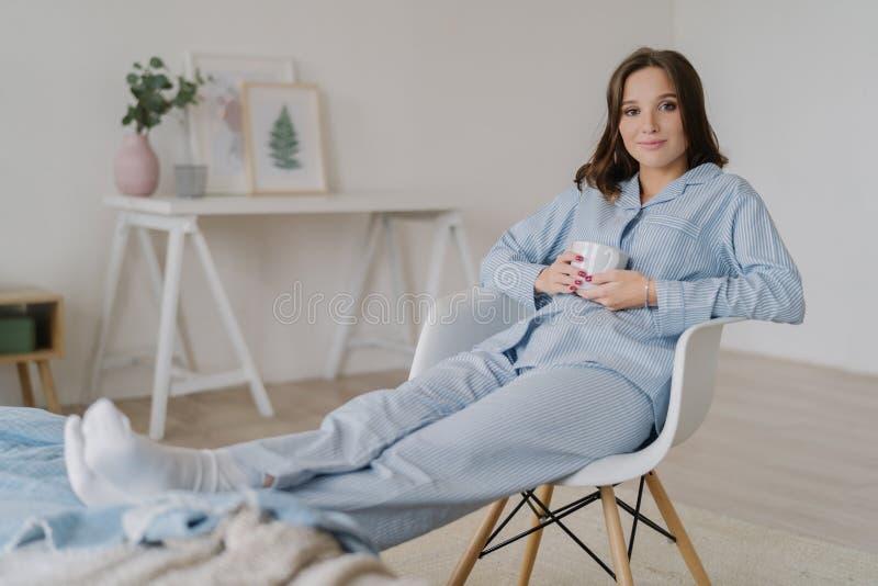 Het binnenschot van ontspannen wijfje gekleed in pyjama, zit op stoel, houdt benen op bed, drinkt hete koffie, stelt tegen binnen royalty-vrije stock afbeelding