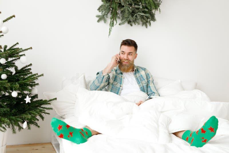 Het binnenschot van positief aantrekkelijk gebaard mannetje gekleed in toevallig geruit overhemd en groene sokken, heeft telefoon royalty-vrije stock afbeeldingen