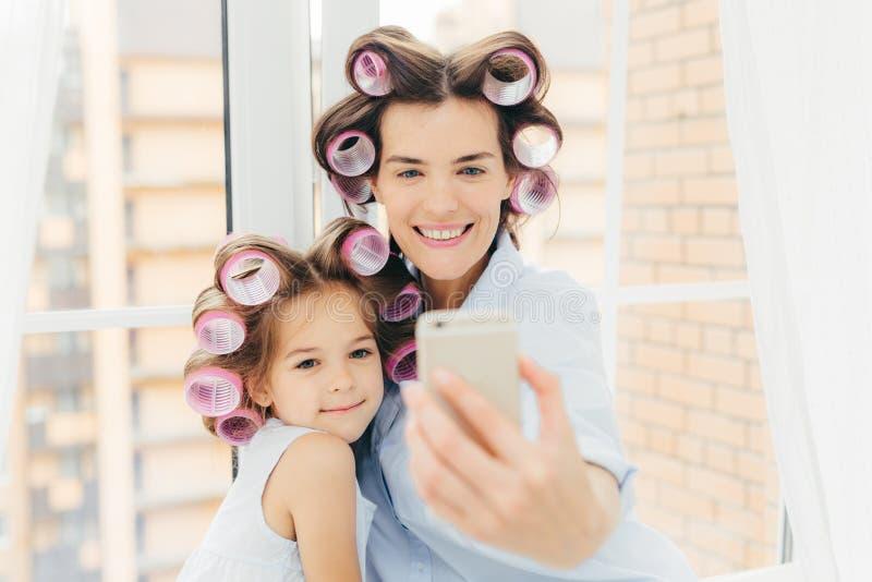 Het binnenschot van het prettige kijken mum met positieve uitdrukking en haar dochter doen krullende kapsels, stellen voor selfie royalty-vrije stock afbeelding
