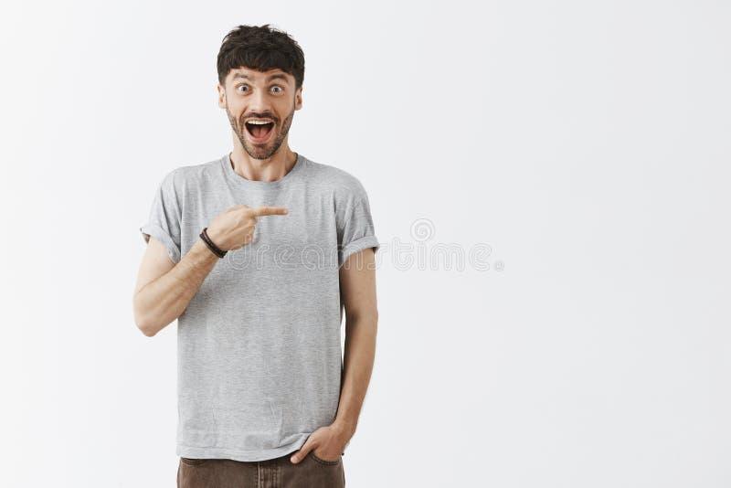 Het binnenschot van verbaasde positieve en gelukkige aantrekkelijke Kaukasische gebaarde kerel in grijze t-shirtholding dient zak royalty-vrije stock fotografie