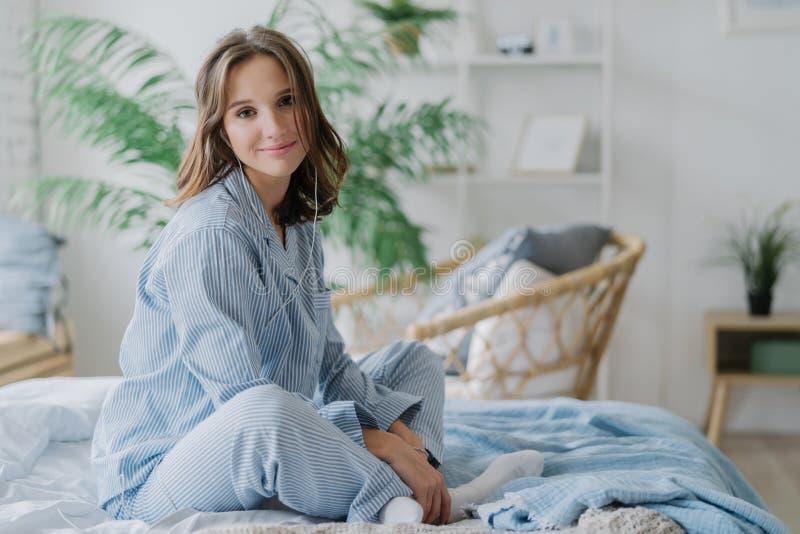 Het binnenschot van vrij donkere haired vrouw zit gekruiste benen op bed, gekleed in nighclothes, witte sokken, bekijkt direcltly royalty-vrije stock afbeelding