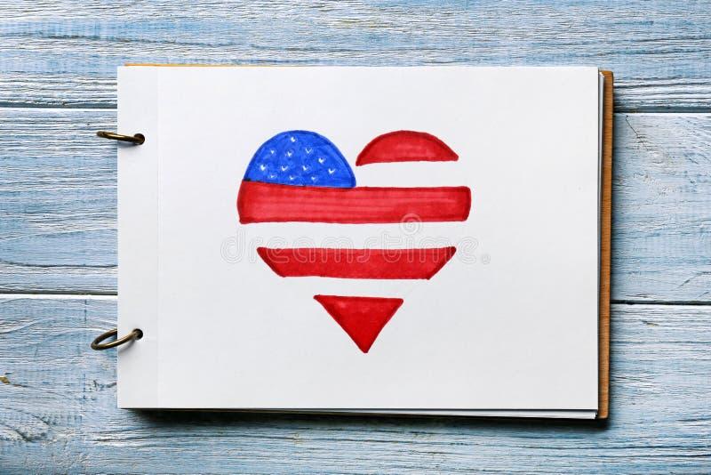 Het blad van document met hart vormde tekening van Amerikaanse nationale vlag op houten lijst stock afbeeldingen