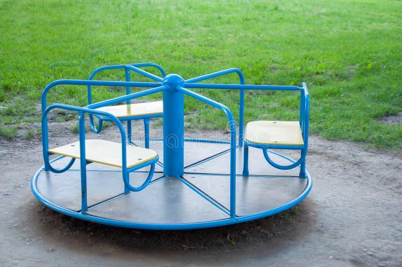 Het blauw van de de schommelingscarrousel van kinderen Bij de speelplaats Op de achtergrond van groen gras stock fotografie
