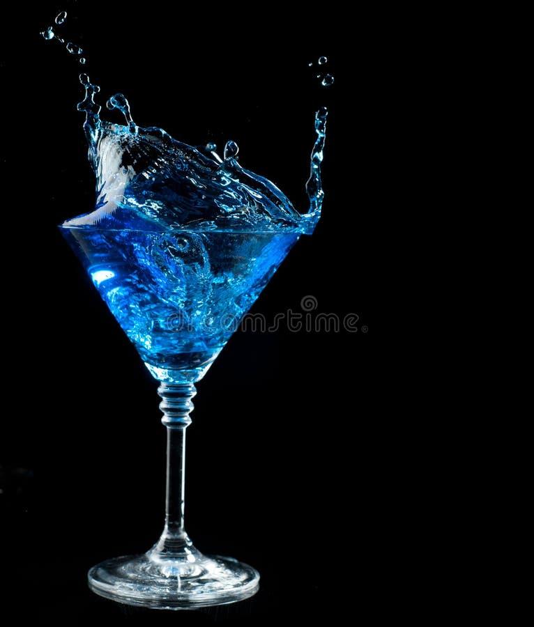 Het blauwe cocktail bespatten in glas op zwarte royalty-vrije stock afbeelding