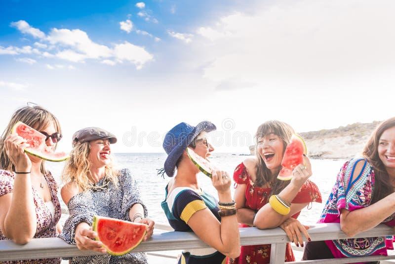 Het blauwe en rode kleurenbeeld van groep wijfjesvrienden blijft samen en heeft pret in de zomer etend een watermeloen Glimlachen royalty-vrije stock afbeelding