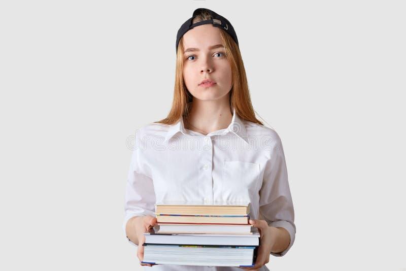 Het blauwe eyed charmante schoolmeisje heeft ernstige gelaatsuitdrukking, die houdend bos van diverse boeken in beide handen zich stock foto