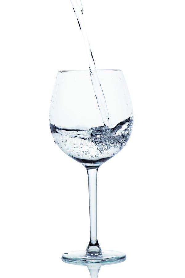 Het blauwe gekleurde water giet in het wijnglas stock foto