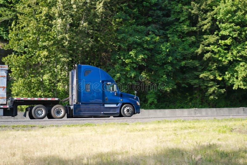 Het blauwe grote profiel die van de installatie semi vrachtwagen met semi aanhangwagen op r gaan stock afbeeldingen