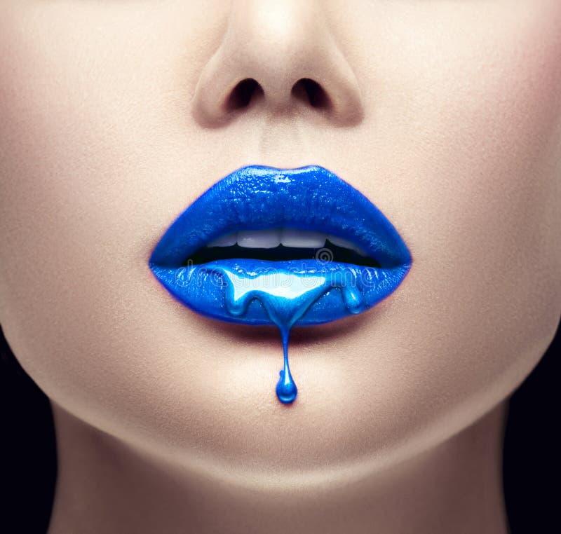 Het blauwe lippenstift druipen Lipgloss die van sexy lippen, Blauwe vloeibare dalingen op de mond van het mooie modelmeisje, crea royalty-vrije stock foto's