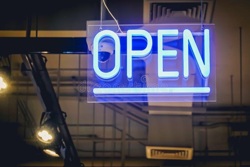 Het blauwe Open teken van de neonlichtkleur op een glasvenster voor bedrijfsvoorzijde van winkel stock foto's