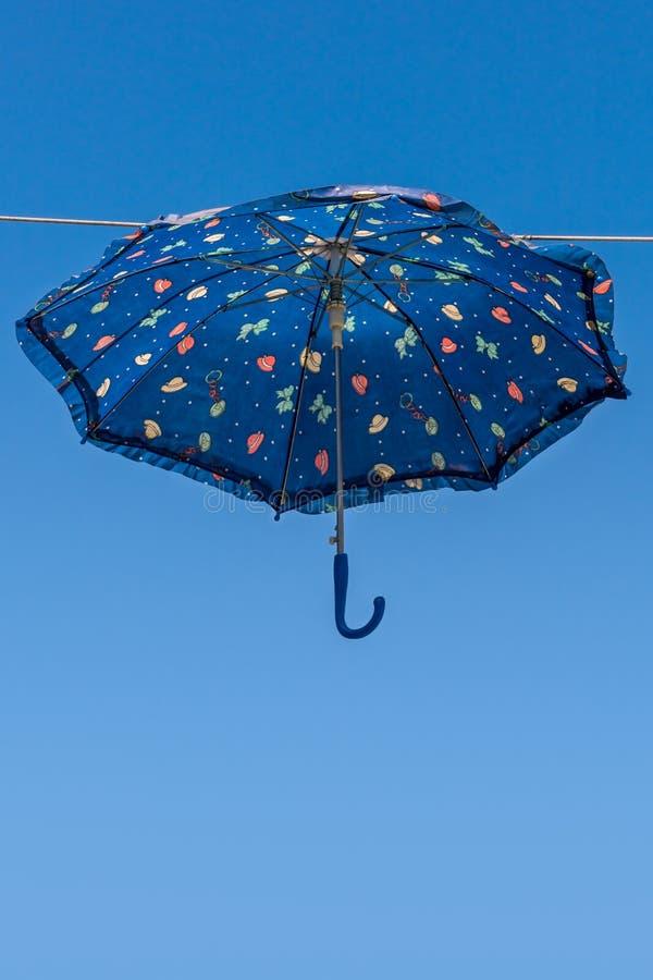 Het blauwe paraplu hangen boven straat royalty-vrije stock fotografie