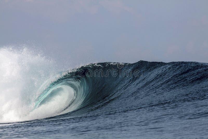 Het blauwe tropische het surfen golf breken over koraalrif stock foto