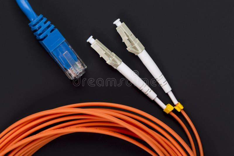 Het blauwe verdraaide koord van het paarflard met de oranje kabel van de vezeloptica op donkere achtergrond stock foto's
