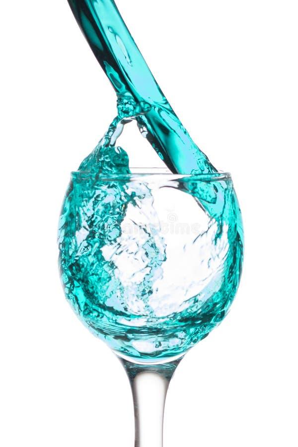Het blauwe vloeibare uitgieten van wijnglas royalty-vrije stock fotografie
