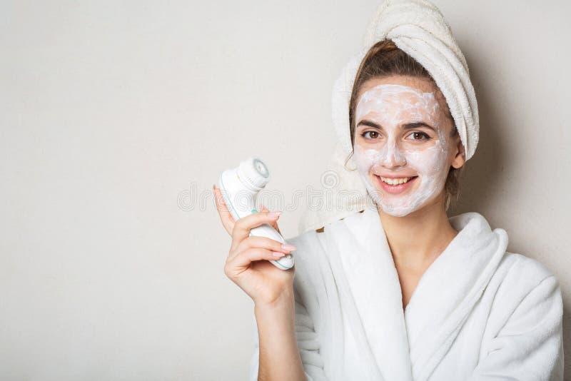 Het blije donkerbruine model stellen met bevochtigende roommasker en gezichtsreinigingsmachine Lege ruimte stock foto's