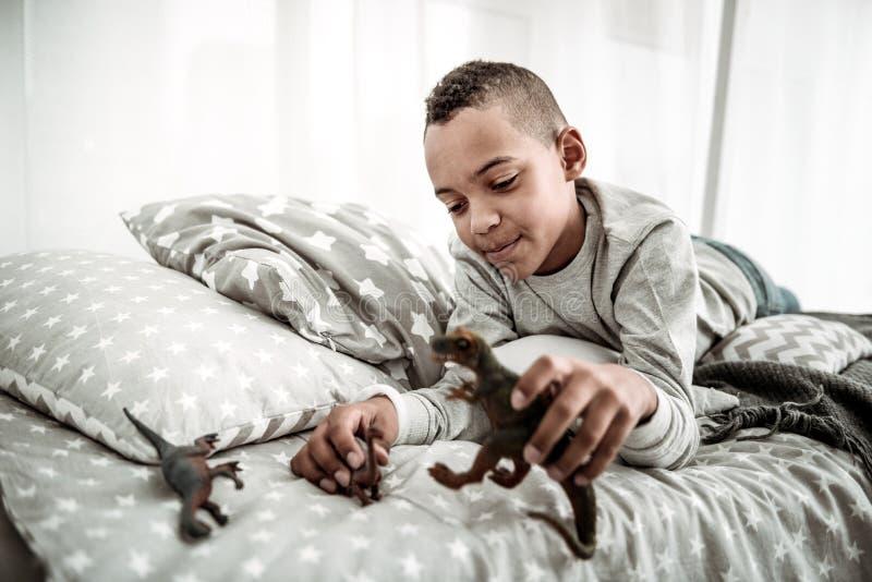Het blije gelukkige jonge jongen spelen met dinosaurussen royalty-vrije stock fotografie