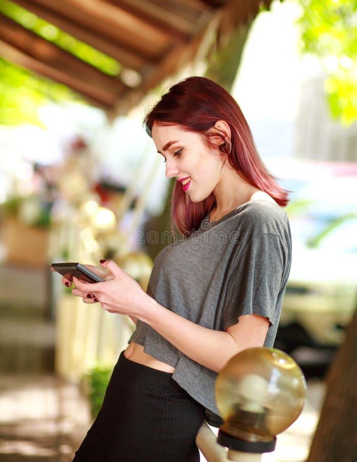 Het blije jonge tienermeisje communiceert op tabletcomputer in de zomerkoffie stock fotografie